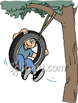 Boy Swinging In a Tire Swing Tied to a Tree