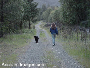 Stock Photo of Girl and Dog Walking Down a Country Road