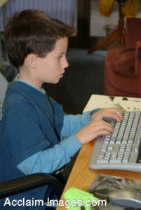 Stock Picture of a Yound Boy Typing at a Computer