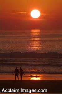 Stock Photo of Lovers Taking a Stroll on the Beach at Sunset
