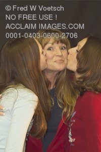 Stock Photo of  Daughters Kissing Their Mother