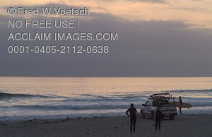 Stock Photo of Surfers and a Lifeguard Truck on a Beach