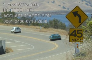 Stock Photo of Cars and an Advisory Speed Sign on a Highway