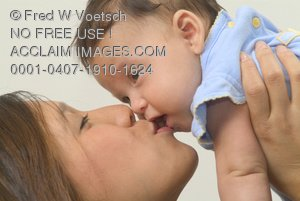 Stock Photo of a Mother Holding Her Baby Up While She Kisses Her