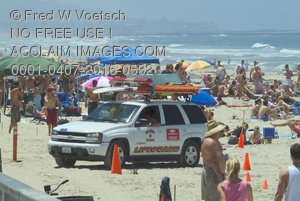 Stock Photo a Lifeguard Vehicle Parked on a Crowded Beach