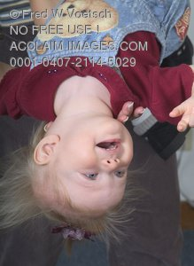 Stock Photo of a Baby Girl Being Held Upside Down