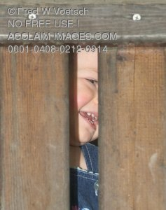 Stock Photo of a Child As Seen Through Two Wooden Boards