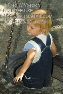 Stock Photo of a Toddler Getting Onto a Tire Swing