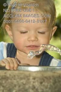Stock Photo of a Blond Girl Playing With a Water Fountain