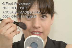 Stock Photo of a Woman Applying Blush On Her Cheeks