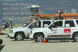 Stock Photo of Two Lifeguard Vehicles and a Lifeguard Tower on a Beach