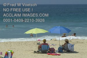 Clip Art Stock Photo of People Relaxing On the Beach Under Umbrellas