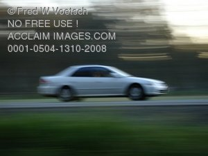Car in Motion Driving Down the Highway Clip Art Photo