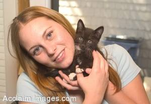 Stock Photo of a Young Woman Holding a Black Kitten