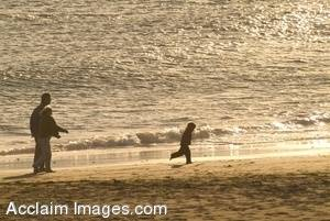 Stock Photo of Parents and Child Walking On The Beach