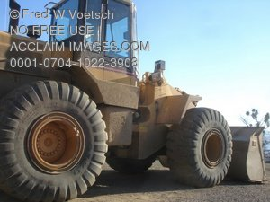 Stock Photo Clip Art of a Yellow Front Loader Used in a Quarry