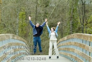 Stock Photograph of a Young Couple Jumping for Joy as They Cross a Bridge in Life
