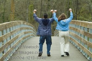 Stock Photo Clip Art of a Young Couple Walking Across a Bridge Cheering