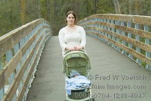 Young Mother Pushing a Stroller Across a Bridge In a Stock Photo