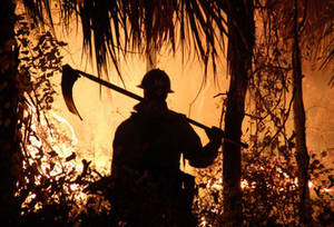 Free Picture of Firefighter In Silhouette Against Orange Fire Haze