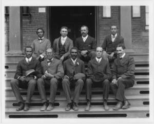 Free Black and White Photo of George Washington Carver With Staff, Seated on Brick Steps, 1902