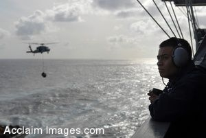 Clipart Photograph of A Sailor Watching As a Helicopter With Cargo Arrives