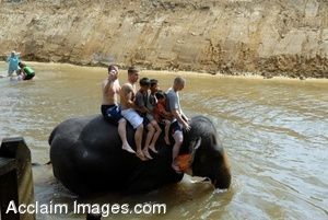 Clipart Photograph of  Kids in Malaysia Riding an Elephant Through Water