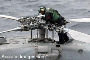 Clipart Photograph of a Soldier Working on the Rotors Of A Helipcopter