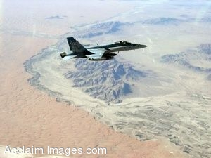 Clip Art Photo of A Military Jet Flying Over Mountains in the Desert