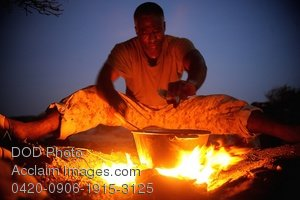 Clip Art Stock Photo of Soldier Cooking Over an Open Fire