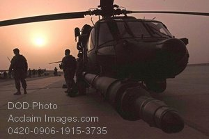 Clip Art Stock Photo of Soldiers Standing by a Military Helicopter at Sunset