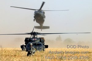 Clip Art Stock Photo of a Soldier Walking in Front of Landing Helicopters