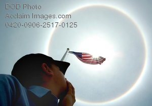 Free Public Domain Picture: Sailor Looking Up at the American Flag With a Halo Rainbow Surrounding It