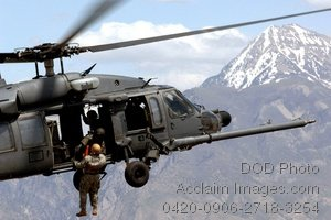 Free Public Domain Picture: Soldier Hanging From a Helicopter Flying Over Mountains