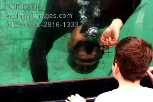 Free Public Domain Picture: Navy Sailor Plays Tic Tac Toe With a Boy Through a Tank Window During Oklahoma City Week