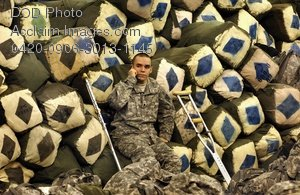 Free Public Domain Picture: Soldier With Crutches Sitting In Front of a Pile of Duffle Bags