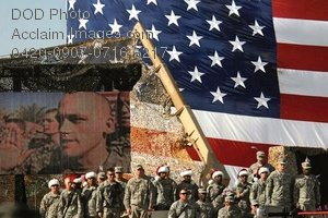 Free Public Domain Picture: Soldiers Gathered In Front of a Huge American Flag and a Mural of Soldiers
