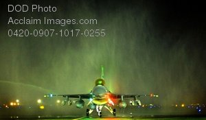 Free Public Domain Picture: Night Landing of an F-16 Fighting Falcon Under the Water Spray of Fire Trucks
