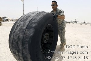 Free Public Domain Picture: Soldier Rolling an Old Globemaster Plane Tire