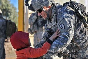 Free Public Domain Picture: Smiling Soldier Picks Up an Iraqi Child Photo