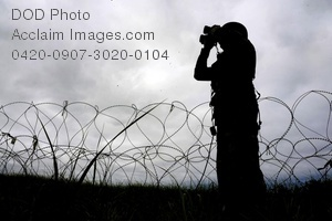 Free Public Domain Picture: Soldier Standing Guard Duty In Front of Barbed Wire Using Binoculars Photo