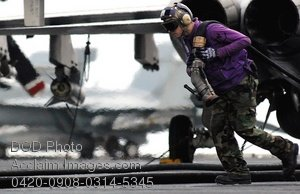 Free Clipart Picture: Airman Pulling a Fuel Hose Across a Flight Deck On An Aircraft Carrier