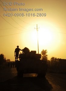 Free Clip Art Picture: Soldier Standing on a Tank at Sunrise Photo