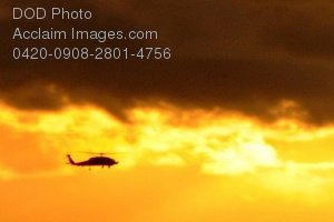 Free Public Domain Picture: Military Helicopter Flying Through a Sunset Filled Cloud Photo