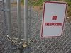 No Trespassing Sign Attached To a Locked Chain Link Fence clipart