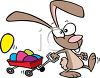 Cartoon of the Easter Bunny Pulling a Wagon Full of Easter Eggs clipart