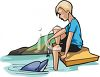 Little Boy Feeding Fish to a Dolphin of a Platform clipart