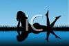Silhouette of a Nude Woman Laying Beside a Lake at Twilight clipart