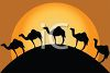 Silhouetted Camels Walking Over a Hill at Sunset clipart