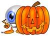 Cartoon Eye Ball Character Beside a Halloween Pumpkin clipart